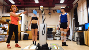 Two Ballet dancers stand in a laboratory with sensors on their bodies
